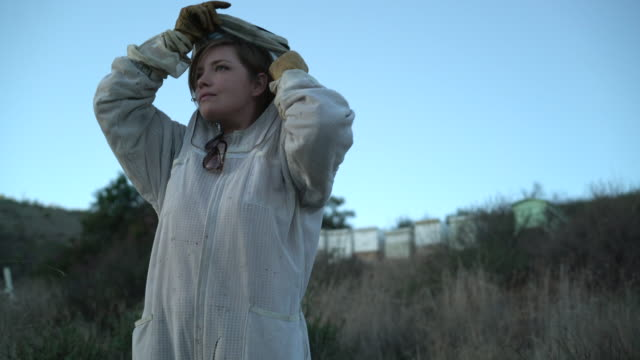 MS Female beekeeper putting on her bee suit