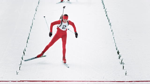 slo mo female biathlon athlete crossing the finish line first - biathlon stock videos and b-roll footage