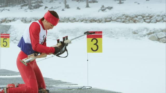 female biathlon athlete shooting in prone position - biathlon stock videos and b-roll footage