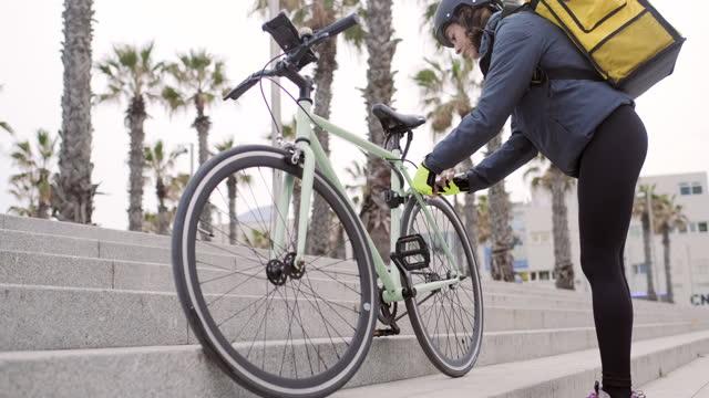 vídeos y material grabado en eventos de stock de mujer repartidora de bicicletas arreglando su bicicleta - trabajador de correos