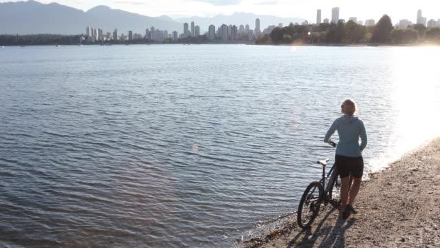 Female bicyclist pushes bike along beach, city skyline behind
