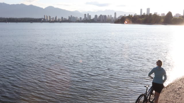 female bicyclist pushes bike along beach, city skyline behind - pacific ocean stock videos & royalty-free footage