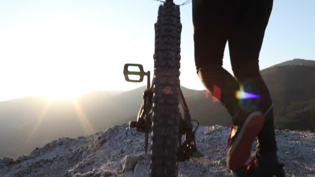 Female biker pushes bike along cliff edge at sunrise