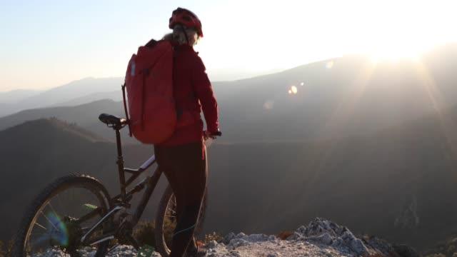 vídeos y material grabado en eventos de stock de mujer ciclista empuja bike a lo largo del acantilado al amanecer - ropa protectora