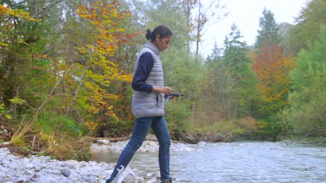 vidéos et rushes de étudiant féminin de biologie mesurant l'oxygène dissous dans la rivière avec un instrument - inclinaison vers le bas