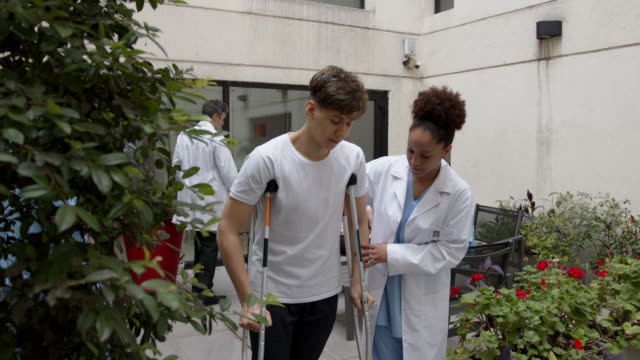 female black therapist helping teenage male patient while he walks with crutches at the patio of physical rehab clinic - crutch stock videos & royalty-free footage