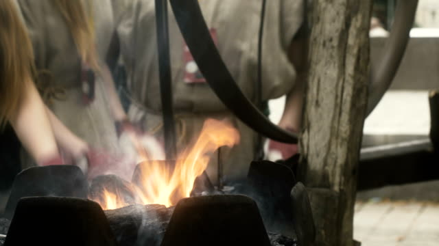 female blacksmiths turn forging wheel - blacksmith stock videos & royalty-free footage