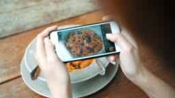 Female blogger photographing lunch in restaurant with her phone. A young woman taking photo of spaghetti food on smartphone, photographing meal with mobile camera.