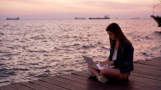 female blogger writing article by the sea - blogging stock videos & royalty-free footage
