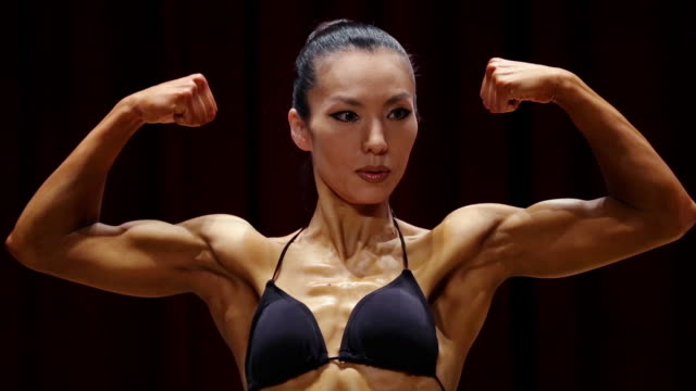 vídeos de stock e filmes b-roll de female body builder posing at bodybuilder championship - body building