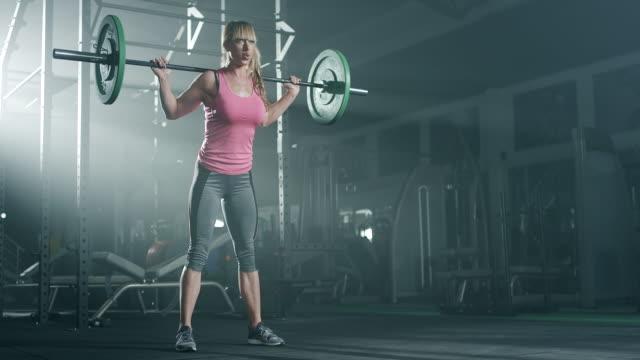 vídeos de stock, filmes e b-roll de fisiculturista feminina fazendo exercício com pesos na academia - peso livre equipamento para exercícios