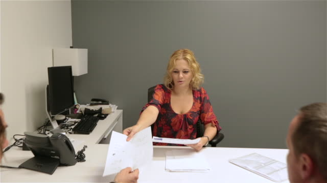 Female boss leads meeting in small private corporate office, hands out paperwork