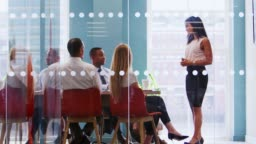 Female boss stands addressing colleagues at business meeting