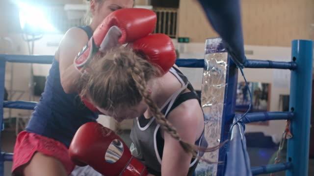 Female boxer beating an opponent