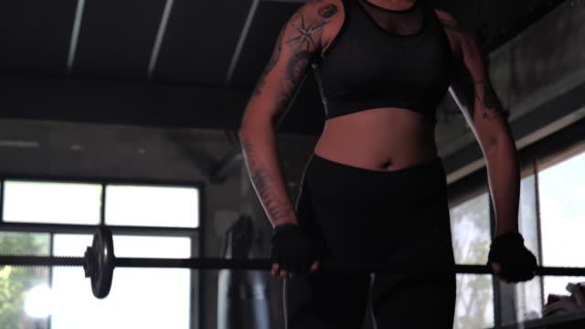 boxer femminile tinto capelli rossi e un tatuaggio sul corpo si stanno allenando attivamente in palestra, adolescente donna asiatica che fa esercizio pesante per le spalle con bilanciere in palestra. - human body part video stock e b–roll