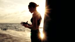 Female boxer getting her fists ready for the boxing gloves by wrapping bandage around them standing against the sun. Young woman wrapping hands with boxing wraps on the beach. Lens flare