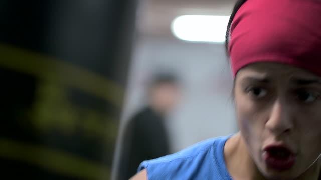 CU of female boxer hitting punching bag