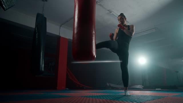 vídeos de stock, filmes e b-roll de pugilista fêmea que retrocede um saco de perfuração - posição de combate