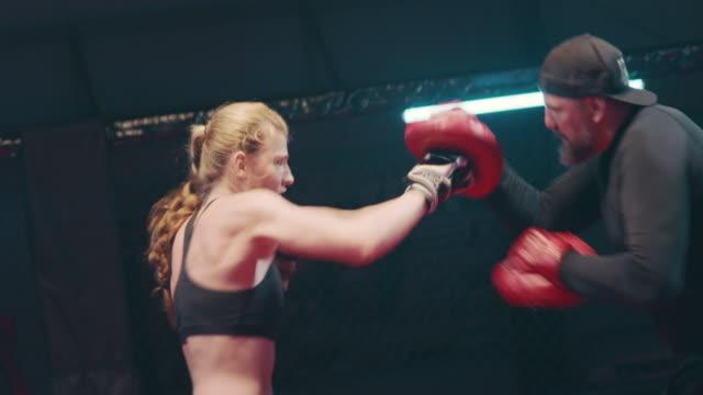 vidéos et rushes de séance de travail de pad de boxeur féminin avec l'entraîneur - agression