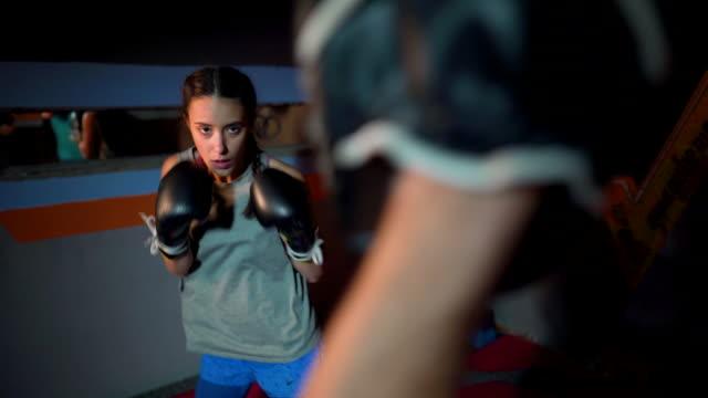 ボクシンググローブでフォーカスミットをパンチする女性ボクサー - 女子ボクシング点の映像素材/bロール