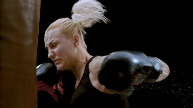 stockvideo's en b-roll-footage met slo mo female boxer punching a heavy bag - stootzak fitnessapparatuur