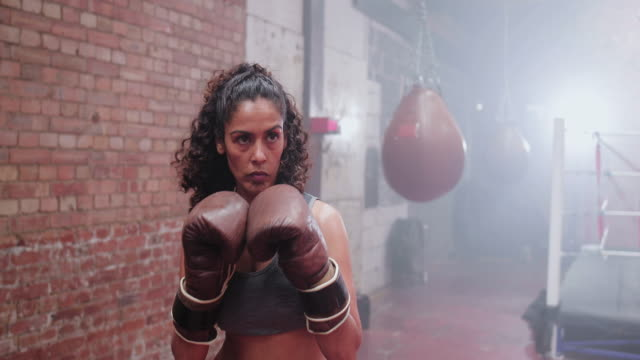 vidéos et rushes de female boxer punching a punch bag - musclé