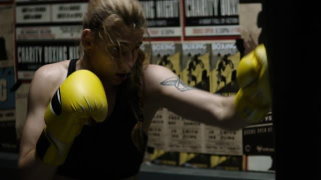 vidéos et rushes de séance de sac de poinçonnage de boxeur féminin - irréductibilité