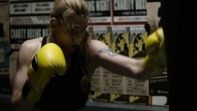female boxer punching bag session - irriducibilità video stock e b–roll