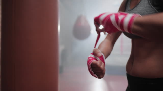 female boxer putting hand wraps on - boxhandschuh stock-videos und b-roll-filmmaterial