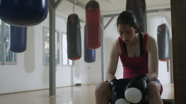 Female boxer resting in boxing gym