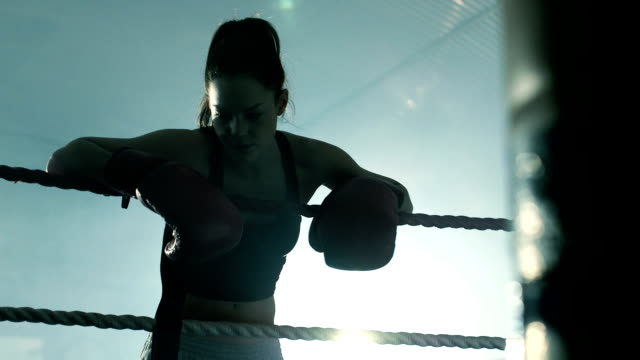 vidéos et rushes de female boxer retreats to the edge of the boxing ring to rest. - s'appuyant