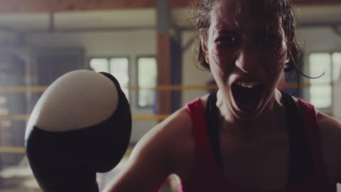 vídeos de stock, filmes e b-roll de fêmea boxer gritando no ringue de boxe depois que venceu uma partida - realização