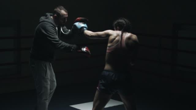 donna pugile sparring con il formatore - allenatore video stock e b–roll