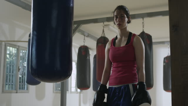 female boxer training with a punching bag - toughness stock videos & royalty-free footage