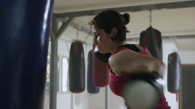 female boxer training with a punching bag - bag stock videos & royalty-free footage