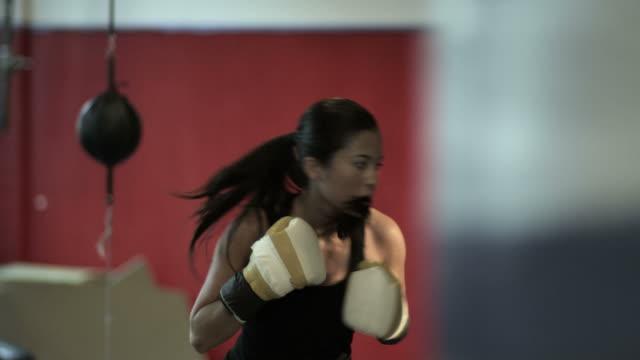 female boxer using heavy bag - 女子ボクシング点の映像素材/bロール