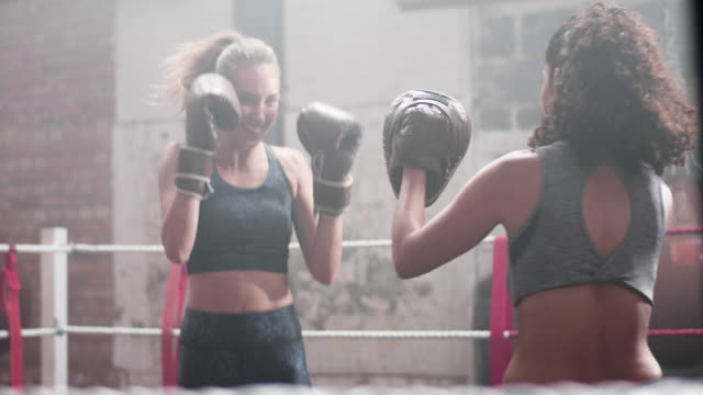female boxer with trainer using focus pads - instructor stock videos & royalty-free footage