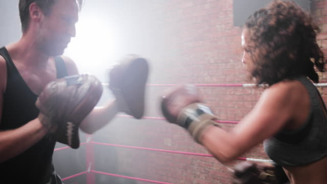 female boxer with trainer using focus pads - diversity stock videos & royalty-free footage