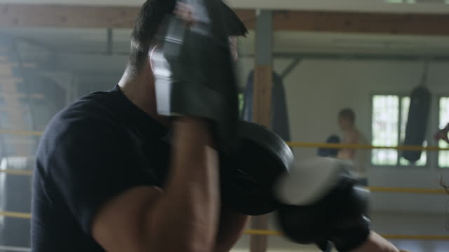 eine boxerin, die arbeit mit einem trainer an box-gym - shorts stock-videos und b-roll-filmmaterial