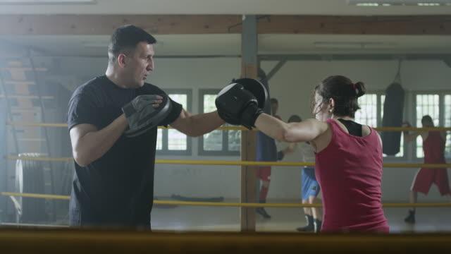 vídeos de stock, filmes e b-roll de um lutador de boxe feminino, trabalhando com um instrutor na academia de boxe - treinador