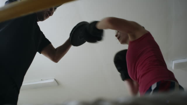 A female boxer working with a trainer at boxing gym