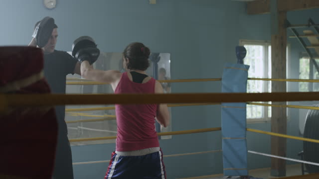 a female boxer working with a trainer at boxing gym - boxing ring stock videos & royalty-free footage