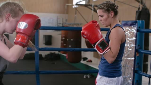 Female boxers finishing training fight