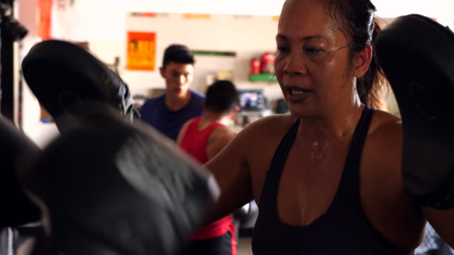 pan female boxers working out together in boxing gym - irriducibilità video stock e b–roll