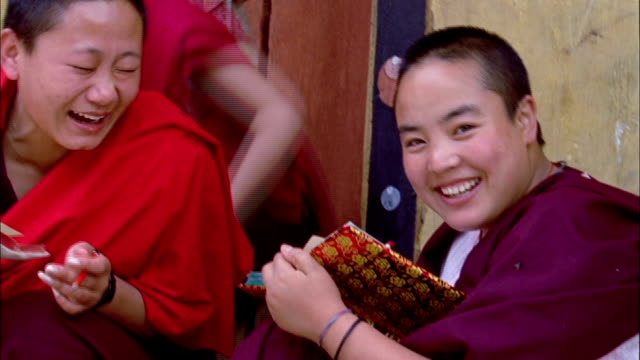 female buddhist monks laughing and smiling as they study together available in hd. - bhutan stock videos & royalty-free footage