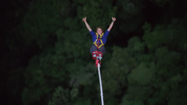 female bungee jumper swings over treetops and gives thumbs up to camera, available in hd. - swinging stock videos & royalty-free footage