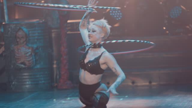 vidéos et rushes de a female burlesque dancer dances seductively with spinning hoops during a circus show - théâtre burlesque