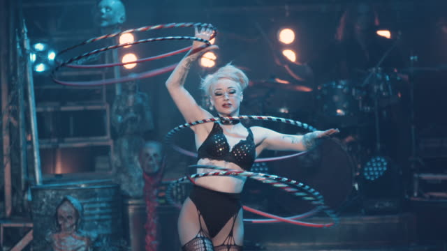 a female burlesque dancer dances seductively with spinning hoops during a circus show - bizarre stock videos & royalty-free footage