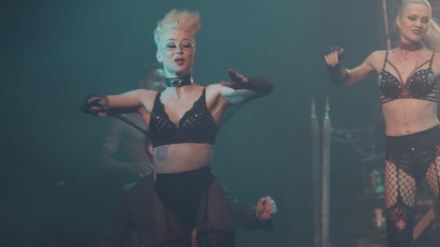 female burlesque dancer performs on stage during a circus show. filmed in slow motion - musical burlesco video stock e b–roll