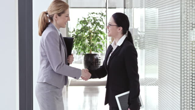 slo mo female business associates shaking hands in hallway - agreement stock videos and b-roll footage